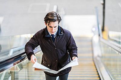 Businessman on escalator reading a newspaper - p300m1581106 by William Perugini