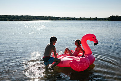 Brother and sister with flamingo pool float on the lake - p300m2143657 by Ekaterina Yakunina