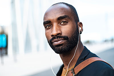 Portrait of bearded young businessman using earphones - p300m2160647 by Josep Suria