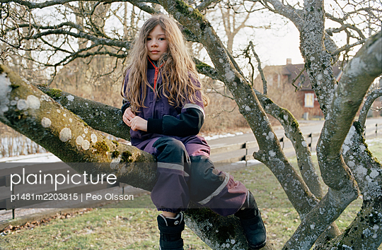 Girl with long hair sitting on branch of tree - p1481m2203815 by Peo Olsson
