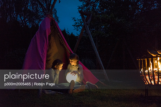 Two girls sitting in tipi, holding lamp as moon - p300m2005465 von Robijn Page