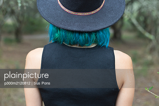 Back view of young woman with dyed blue and green hair wearing black hat - p300m2120812 by Sus Pons