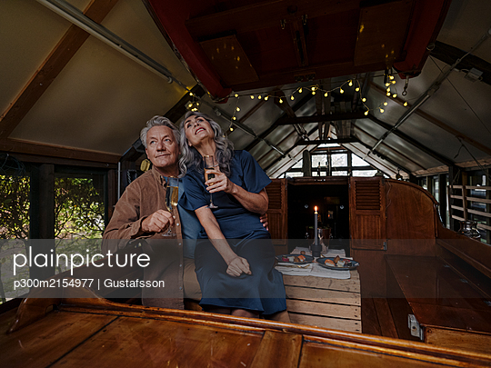 Senior couple having a candlelight dinner on a boat in boathouse - p300m2154977 by Gustafsson