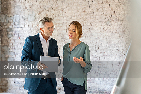 Businesswoman having discussion with architect while working over digital tablet at construction site - p300m2257112 by Peter Scholl
