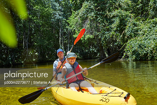 Cheerful daughter kayaking with oar while sitting against father in canoe - p300m2273677 by Stefanie Aumiller