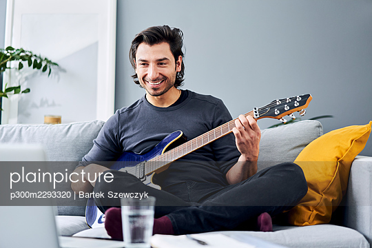 Man looking at laptop while playing guitar on sofa at home - p300m2293320 by Bartek Szewczyk