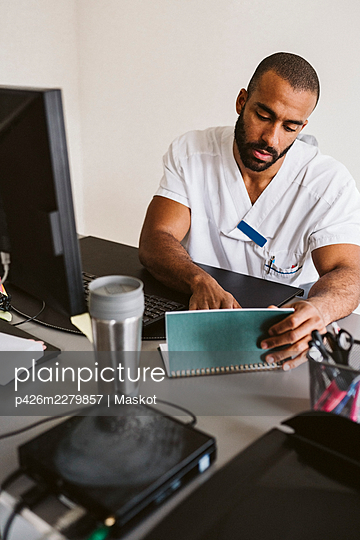Male healthcare worker reading medical record sitting at desk in medical clinic - p426m2279857 by Maskot
