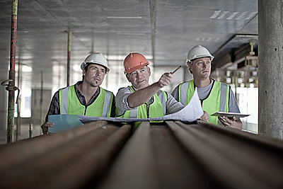 Male construction worker discussing plan with coworkers at construction site - p300m2250302 by LOUIS CHRISTIAN