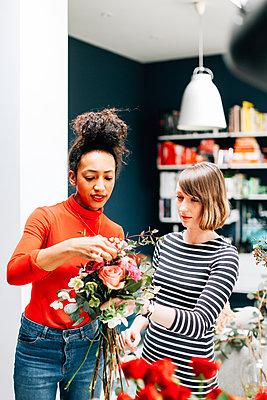 Florist showing student at flower arranging workshop - p429m1418068 by Alys Tomlinson