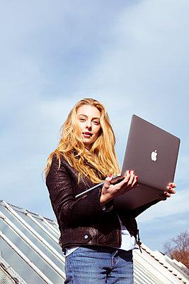 Junge Frau mit Laptop auf Dach - p432m1220800 von mia takahara