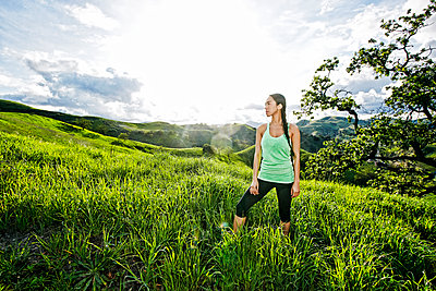 Mixed race athlete standing on rural hillside - p555m1412195 by Peathegee Inc