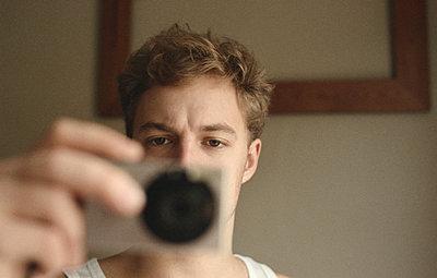 Young man taking photograph - p956m1136866 by Anna Quinn