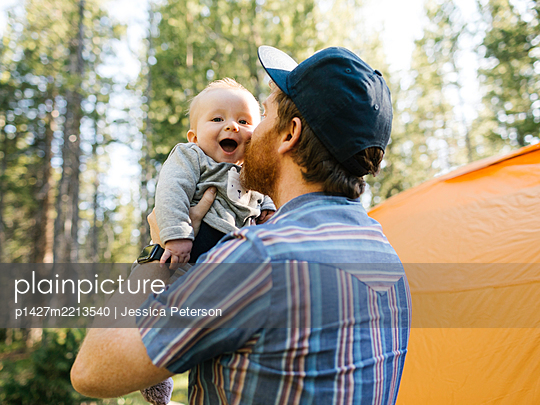 Man kissing baby son (6-11 months) in forest, tent in background, Wasatch Cache National Forest - p1427m2213540 by Jessica Peterson