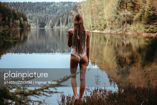 Frau posiert vor ruhigem Bergsee - p1455m2203734 von Ingmar Wein