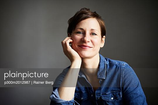 Portrait of ana ttractive woman, wearing denim shirt - p300m2012987 von Rainer Berg