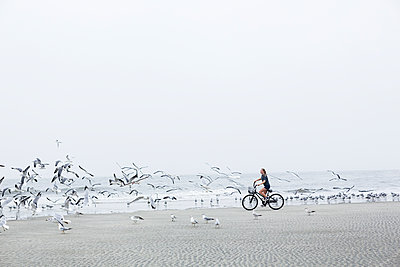 A teenage girl biking on a sandy beach by the ocean - p1100m2164926 by Mint Images