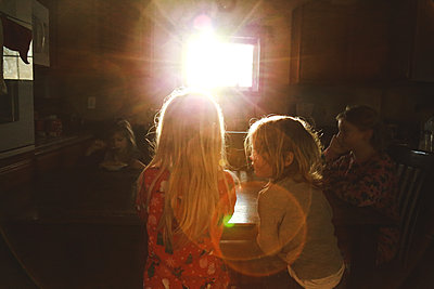 Children eating breakfast at table in morning sunflare - p1166m2171676 by Cavan Images