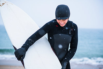 Young woman going winter surfing in snow - p1166m2177051 by Cavan Images