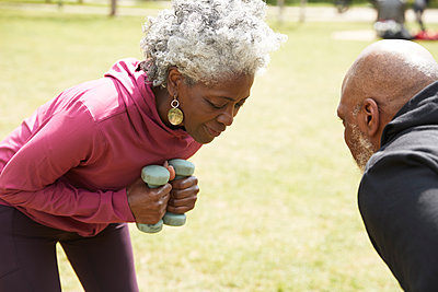 Man looking at woman bending while exercising with dumbbells in public park - p300m2290790 by Pete Muller