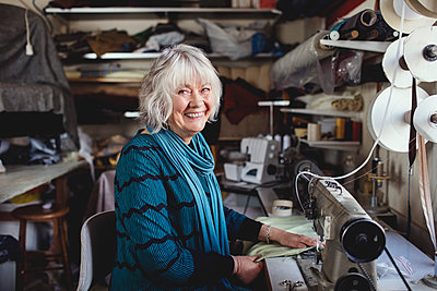 Portrait of smiling senior owner sitting at sewing machine in workshop - p426m1543003 by Maskot