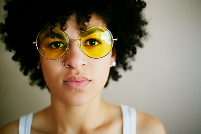 Portrait of serious Mixed Race woman wearing yellow sunglasses - p555m1219601 by Peathegee Inc