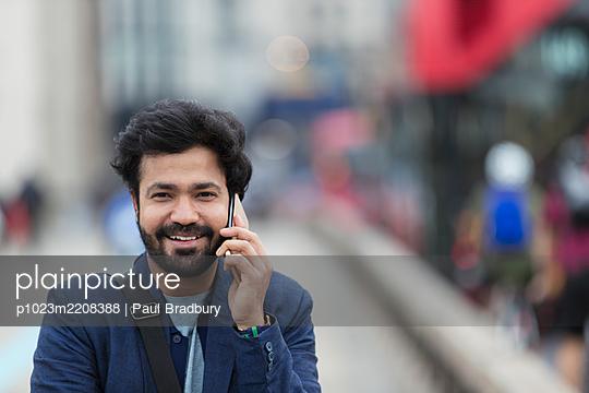 Portrait smiling businessman talking on smart phone outdoors - p1023m2208388 by Paul Bradbury