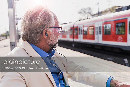 Mature businessman with earbuds sitting at train station - p300m1587243 von Uwe Umstätter