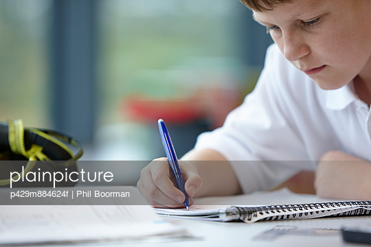 Close up of schoolboy writing in class - p429m884624f by Phil Boorman