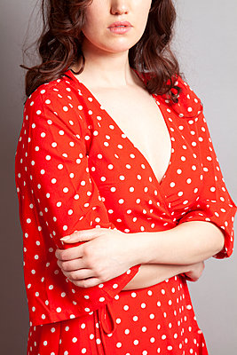Woman in Red Polka Dress with Arms Folded - p1248m1573431 by miguel sobreira