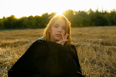Young woman in stubble field in the evening sun - p1646m2249822 by Slava Chistyakov
