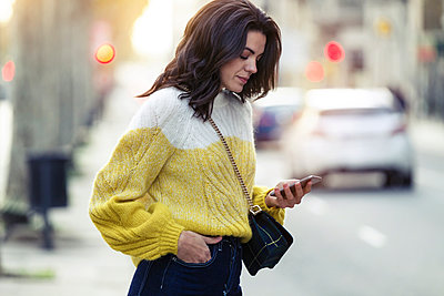 Brunette woman using her smartphone in the city - p300m2140649 by Josep Suria