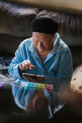 Smiling senior woman using smart phone at home - p300m2243804 by DREAMSTOCK1982