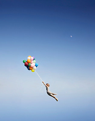 Woman floating away with balloons - p4299208 by Liam Norris