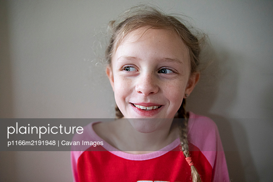 Laughing Blonde Girl With French Braids Looks Off Camera - p1166m2191948 by Cavan Images