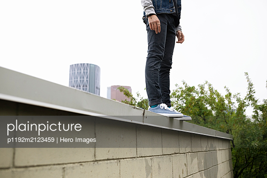 Low section young man standing on urban ledge - p1192m2123459 by Hero Images