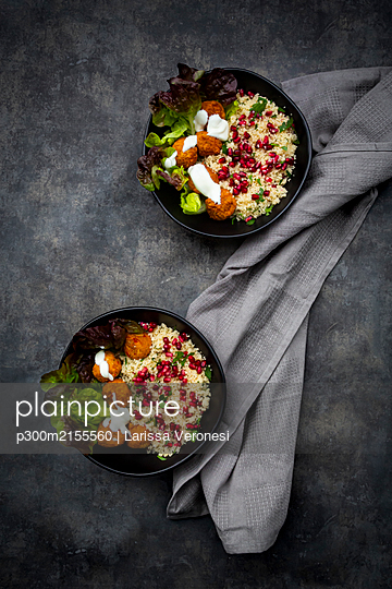 Bowls of falafel with lettuce, yogurt, pomegranate seeds, parsley, mint and Tabbouleh salad - p300m2155560 by Larissa Veronesi