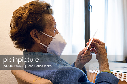 Senior woman in protective face mask looking at photograph - p300m2287532 by Jose Carlos Ichiro