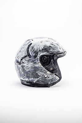 A worn, scratched and damaged black crash helmet on a white background - p1302m2126951 by Richard Nixon