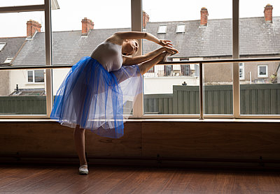 Ballerina practicing ballet dance near window - p1315m2017835 by Wavebreak