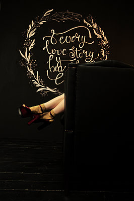 Female feet in shoes comes out of the back of the chair - p1412m1572590 by Svetlana Shemeleva