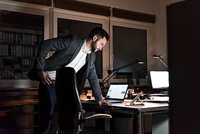 Businessman standing in office at night looking at tablet - p300m1581240 by Uwe Umstätter