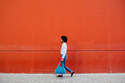 Man with bag walking down the street in front of a red wall - p300m2069991 by Josep Rovirosa