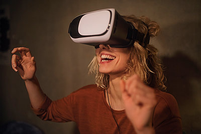 Laughing young woman using Virtual Reality Glasses at home - p300m2119776 by Christian Gohdes