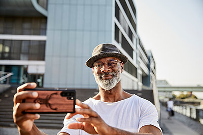 Portrait of smiling mature man with grey beard taking selfies with smartphone - p300m2131873 by Jo Kirchherr