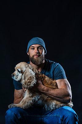 Portrait of a muscular man sitting in studio with a dog - p300m2154690 by Javier De La Torre Sebastian