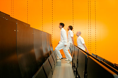 Three men walking up stairs in theatre - p300m2207130 by Michael Bader