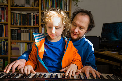 Father teaching synthesizer to son while at home - p300m2277148 by Irina Heß