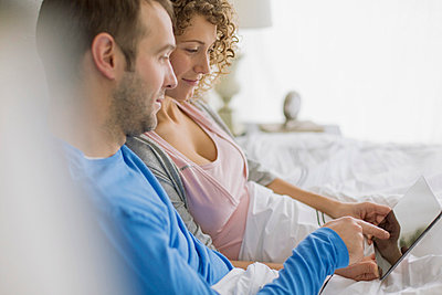 Couple sharing tablet computer in bed together. - p328m840980f by Hero Images