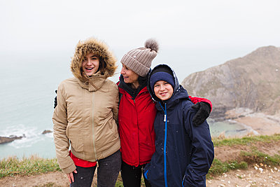 Portrait happy family in warm clothing standing on cliff overlooking ocean - p1023m2024331 by Sam Edwards