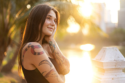 beautiful girl in tattoos among the palm trees at sunset - p1166m2279473 by Cavan Images